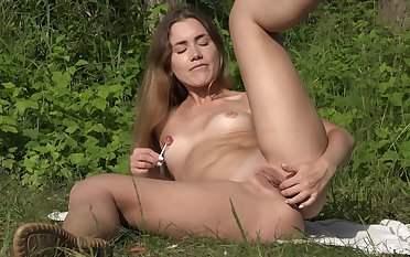 Teen pleases her shaved pussy with soft touches plus a lollipop